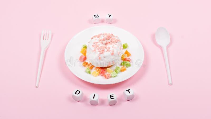 De witte plaat met lepel, vork en Doughnut verfraaide suikerglazuur en bestrooit Ongezonde ongezonde kost Op dieet zijnd, het Gez royalty-vrije stock foto