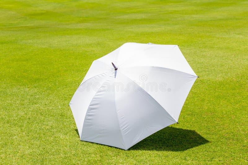 De witte plaats van de zonparaplu op de groene cursus die van het grasgolf FO gebruiken royalty-vrije stock fotografie
