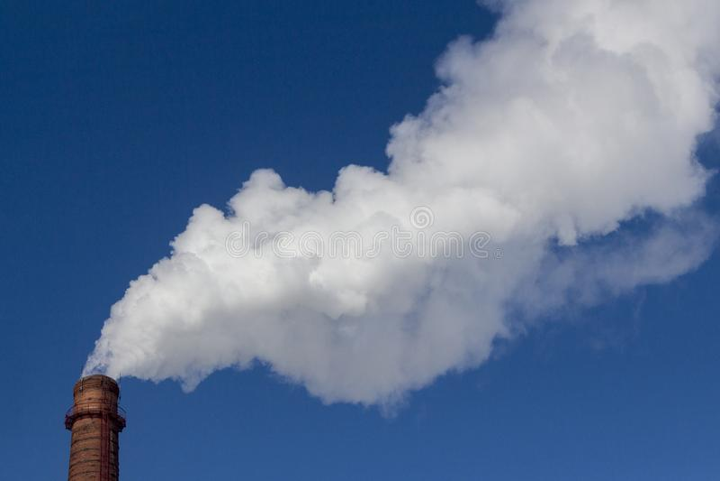 De witte rook komt uit de oude schoorsteen van de baksteenfabriek De conceptenindustrie en milieubescherming stock foto