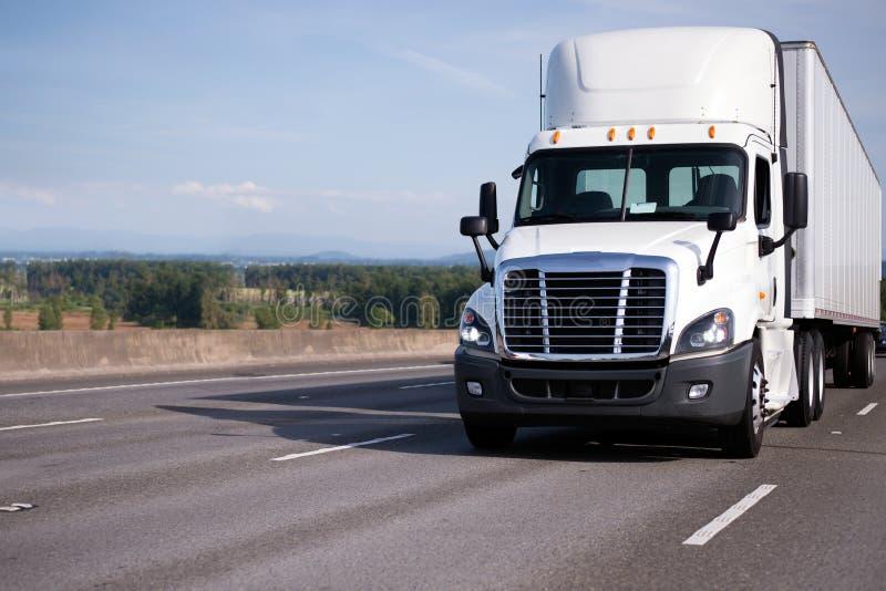 De witte semi vrachtwagen met de hoge cabine van de dakdag en de semi aanhangwagen bewegen zich  royalty-vrije stock fotografie
