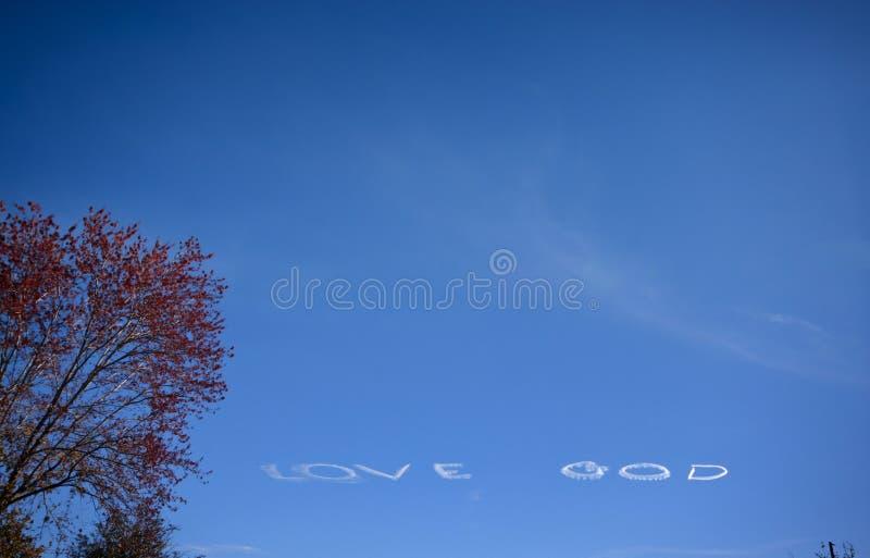 De witte tekst van de GOD van de LIEFDE die bij blauwe hemel wordt gecre?ërd royalty-vrije stock foto