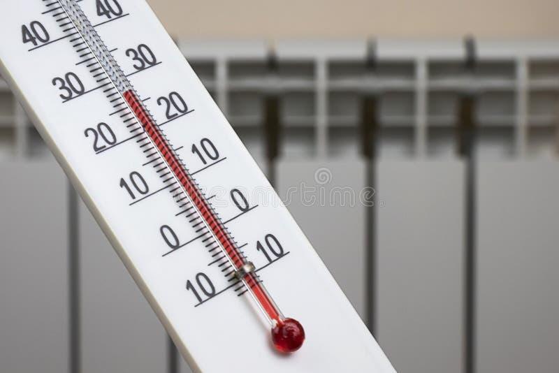 De witte thermometer van de alcoholruimte toont een comfortabele temperatuur in het huis tegen de achtergrond van een het verwarm stock foto's