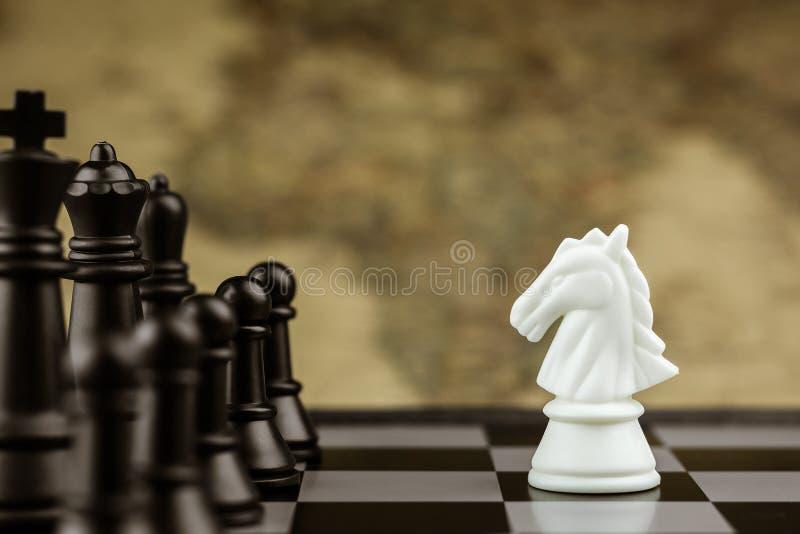 De witte tribune van het paardschaak ontmoet zwarte vijand op een schaakbord - Bedrijfswinnaar en strijdconcept stock afbeeldingen
