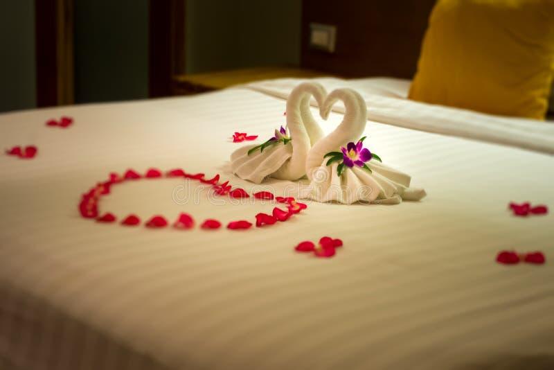 De witte twee handdoekzwanen en rood namen bloemblaadjes op het bed, Wittebroodswekendecoratie toe royalty-vrije stock foto