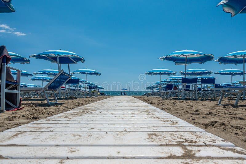 de witte weg op de strandlood rechtstreeks aan het water en is links en net daar sunbeds en parasols stock afbeeldingen