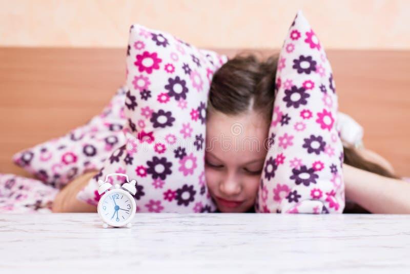 De witte wekker bevindt zich op de lijst aangaande de achtergrond die van een meisje haar oren behandelen met hoofdkussens stock fotografie