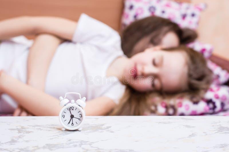 De witte wekker bevindt zich op de lijst aangaande de achtergrond van twee slaapmeisjes in bed royalty-vrije stock afbeeldingen