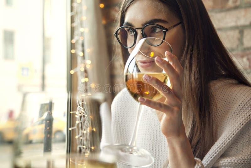 De witte wijn van de vrouwendrank dichtbij venster in restaurant stock foto