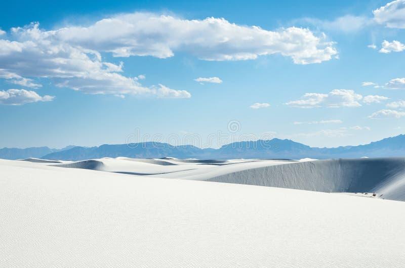 De witte zandduinen in helder daglicht en verre bergen stock fotografie