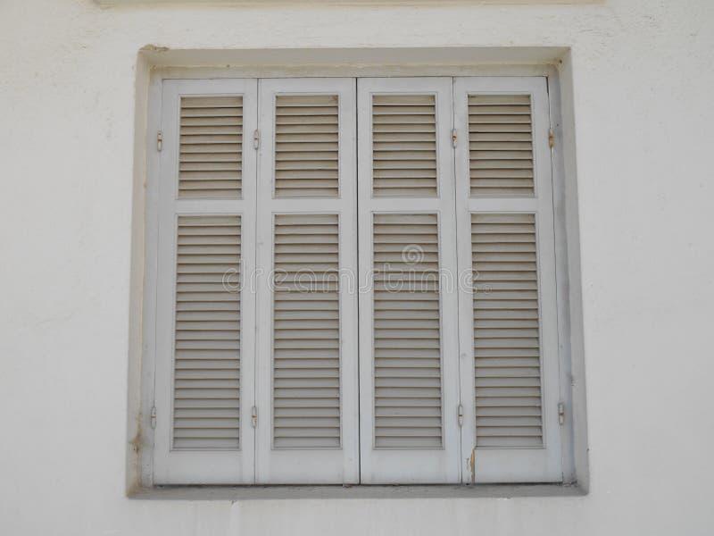De witte zonneblinden op venster met lichte huid stemmen muren royalty-vrije stock fotografie