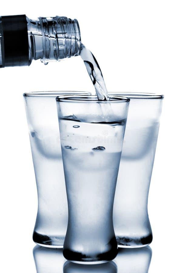 De wodka giet in glas stock foto's