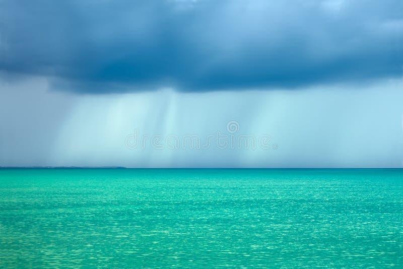 De wolken van de onweersregen over het turkooise overzees stock foto