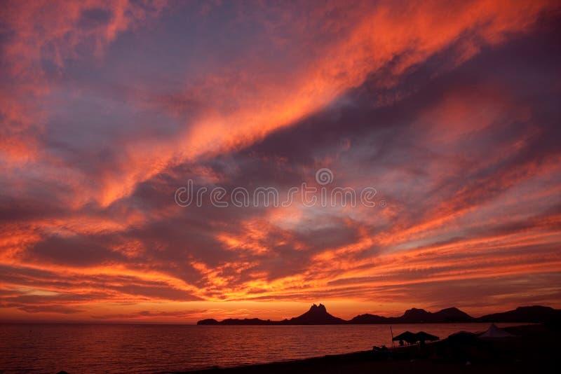 De wolken van de zonsondergang bij kust stock foto