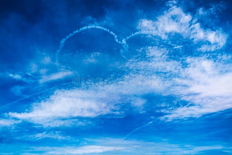 De wolkentekening van het liefdehart door vliegtuig op airshow Liefdeconcept voor het reizen van de wereld stock fotografie