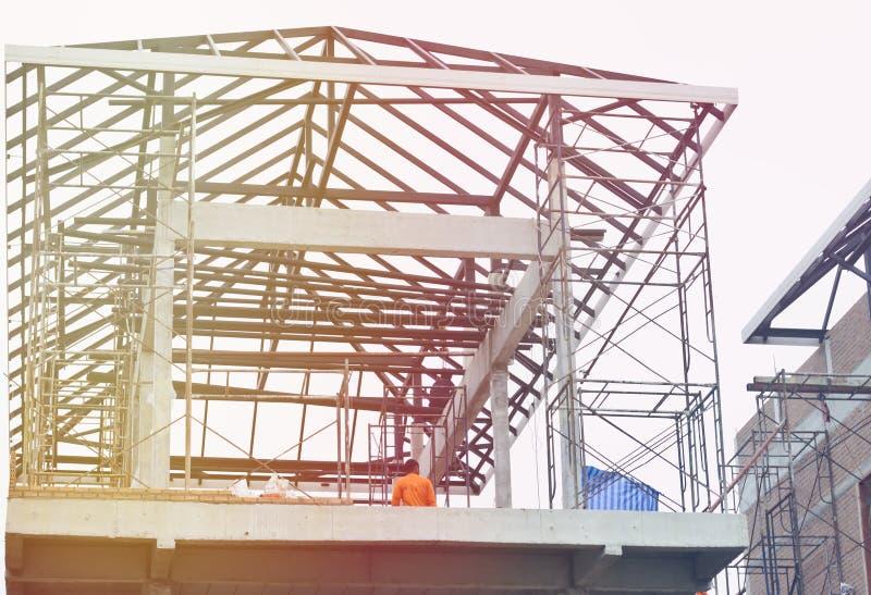 De woningbouw zag het staaldak omhoog het kijken structureren om de bouwvakkers op de hogere vloer te zien, stock afbeeldingen