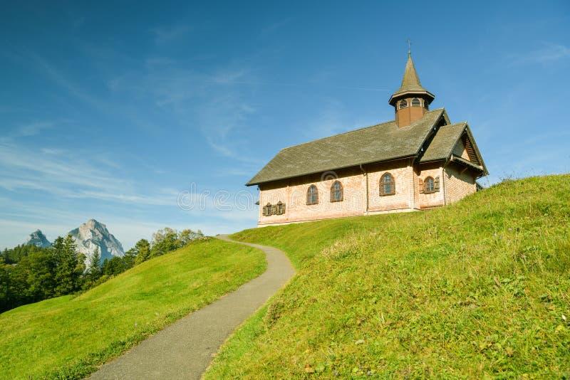 De Woodenkerk in het dorp Stoos met mooie Grosser Mythen piek op de achtergrond stock afbeelding