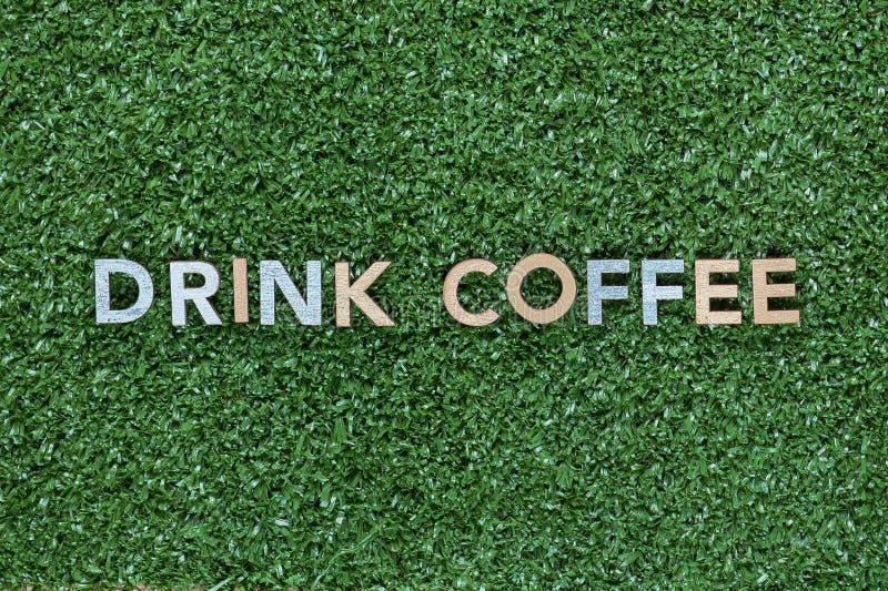 De woorden drinken koffie van multicolored brieven op grasachtergrond hierboven wordt, schot van, in het centrum wordt gericht ge stock fotografie