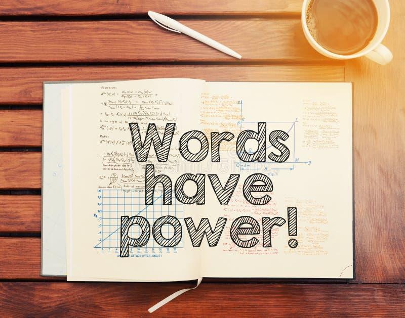 De woorden hebben macht: tekst binnen notitieboekje op lijst met koffie stock afbeelding