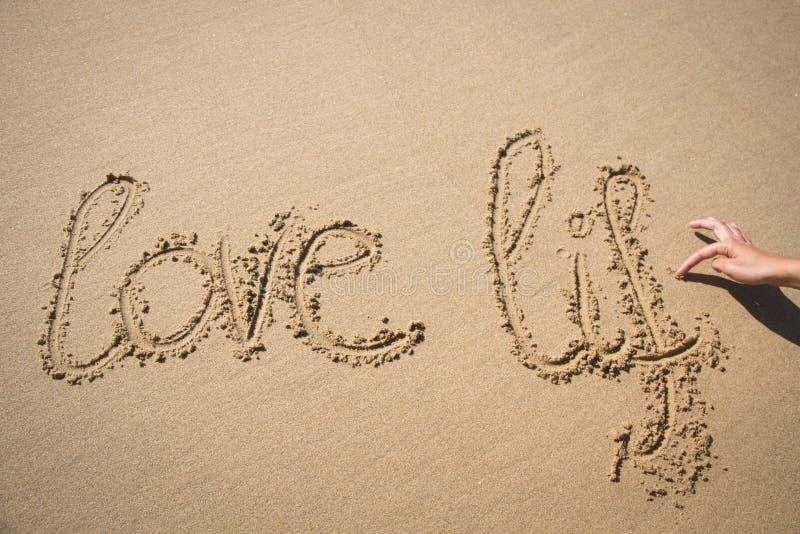 De woorden houden van het leven dat in het zand wordt geschreven stock foto's