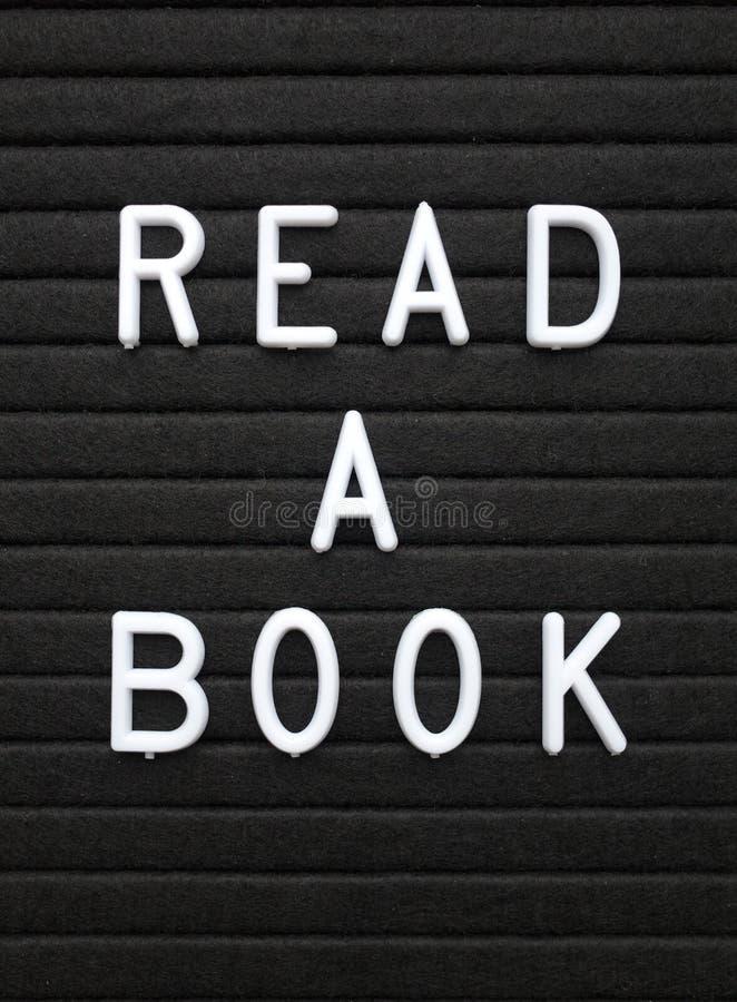 De woorden lezen een Boek in witte teksten op een zwarte brievenraad stock fotografie
