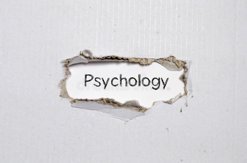 De woordpsychologie die achter gescheurd document verschijnen stock foto's