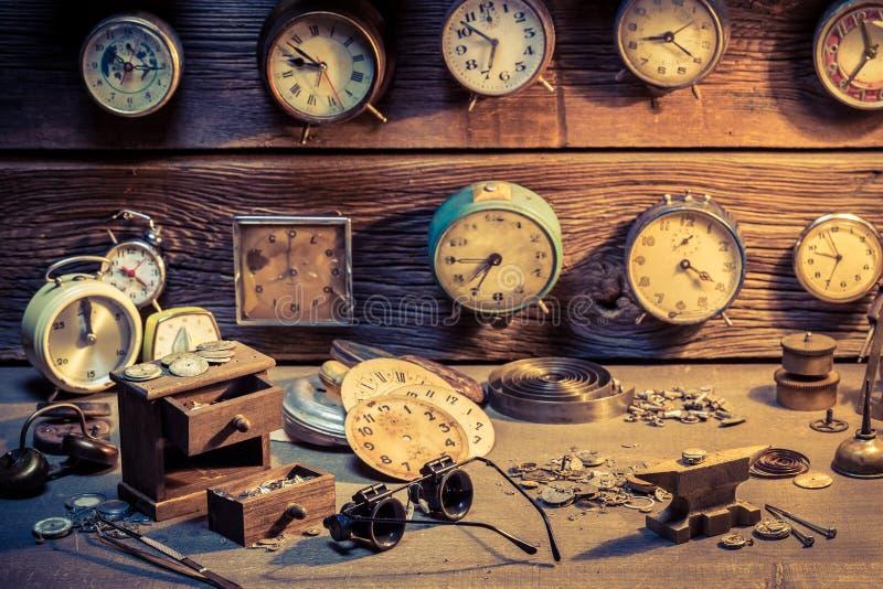 De workshop van de horlogemaker met delen van klokken stock afbeelding