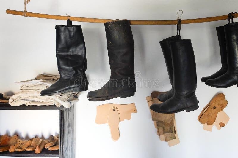 De workshop van de oude schoenmaker met hulpmiddelen stock foto