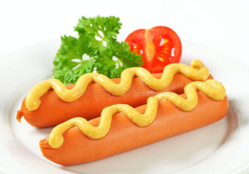 Frankfurterworsten met mosterd stock foto
