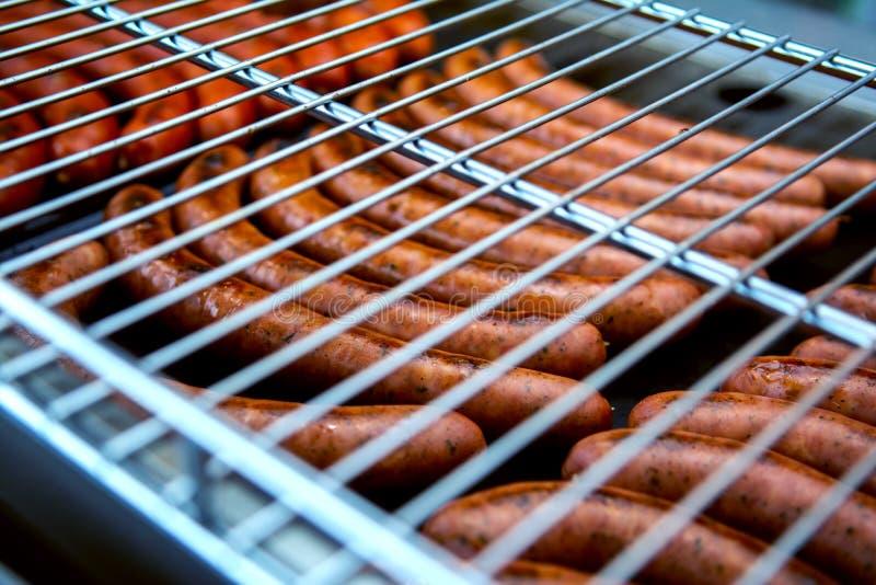 De worsten worden geroosterd Kokende worstenbarbecue Snel voedsel Roosterbbq stock afbeeldingen