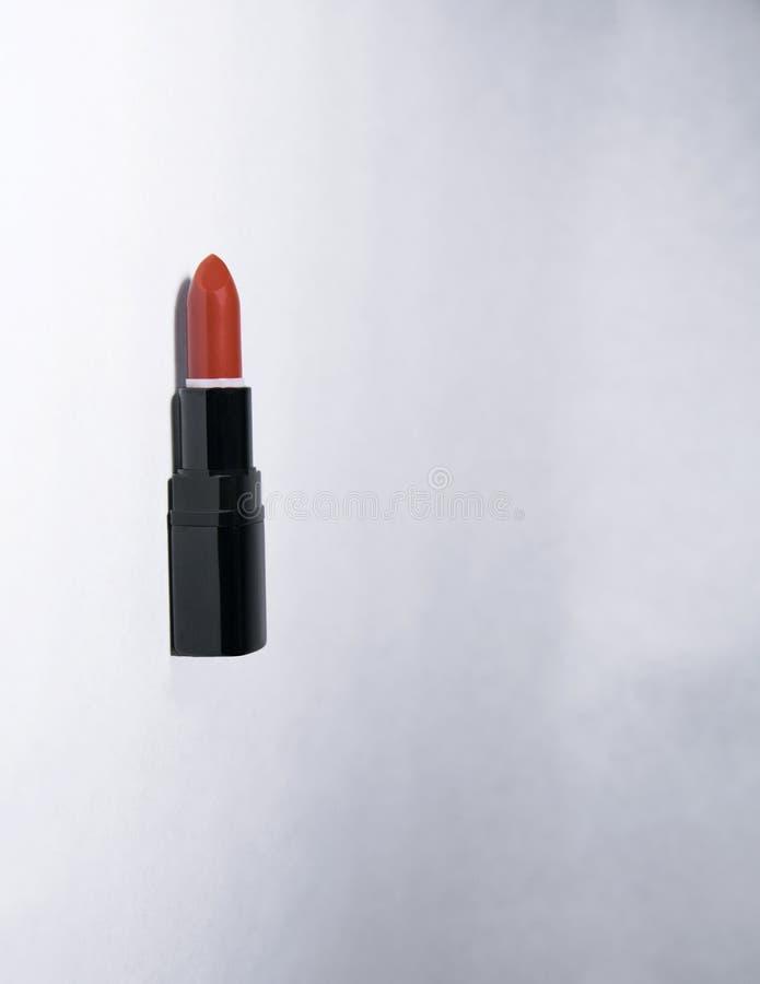 De wortel-gekleurde verticale lippenstift ligt op een witte achtergrond open zonder een GLB in een zwart geval stock foto