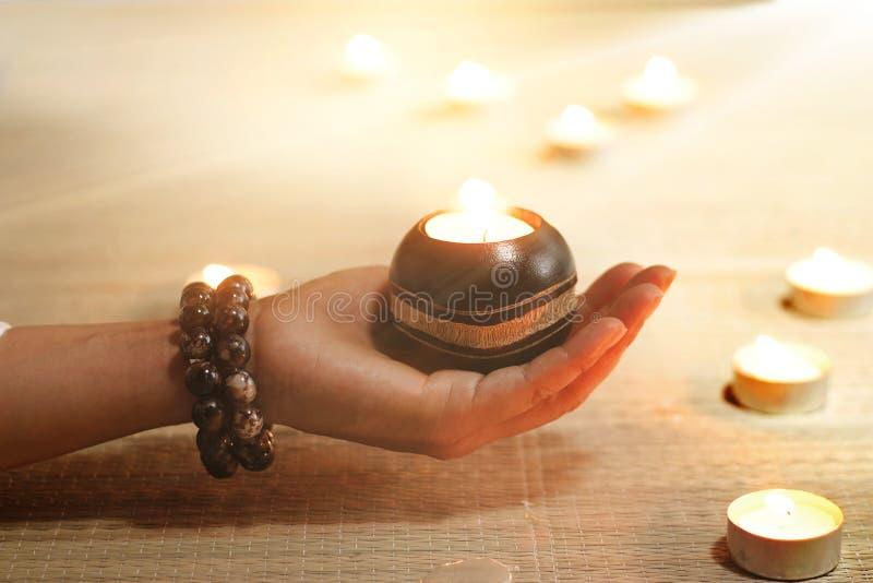 De yoga en de meditatie de lampen van de holdingsolie van de vrouwenhand in tempel stock afbeelding