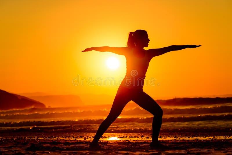 De yoga en ontspant op strand bij zonsondergang royalty-vrije stock afbeelding