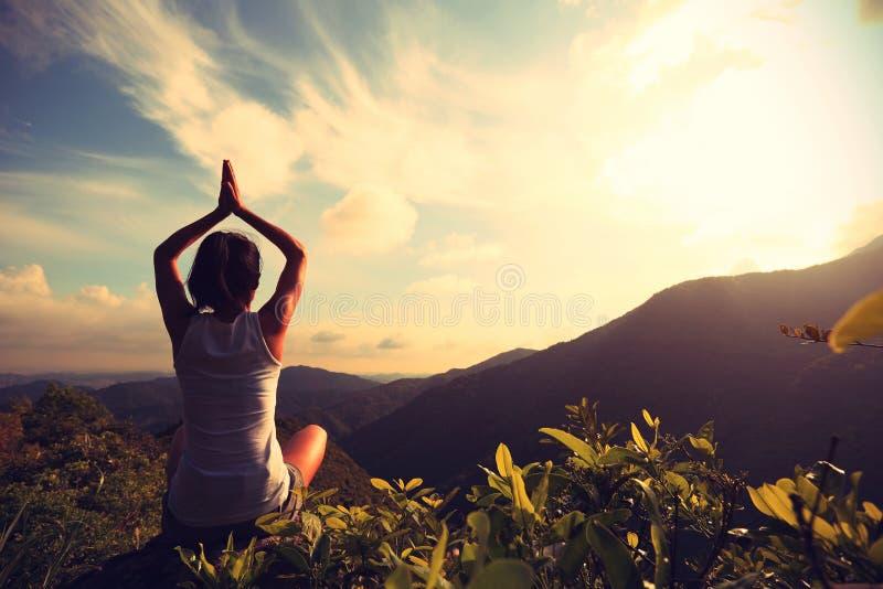 De yoga van de vrouwenpraktijk bij bergpiek royalty-vrije stock afbeelding
