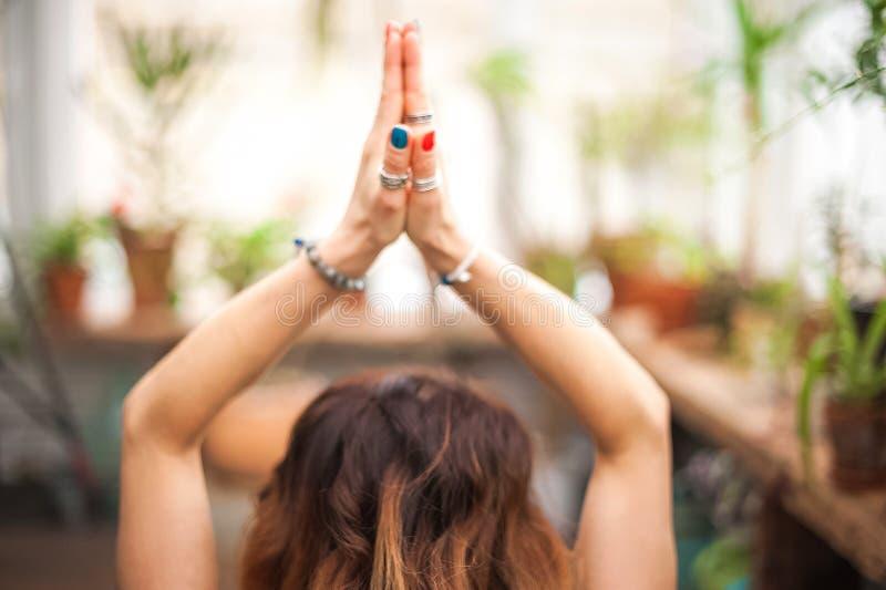 De yoga van handenasana De yoga van meisjespraktijken in bloemen thuis close-up Meditatie, handen, met de hand gemaakte armband royalty-vrije stock afbeeldingen