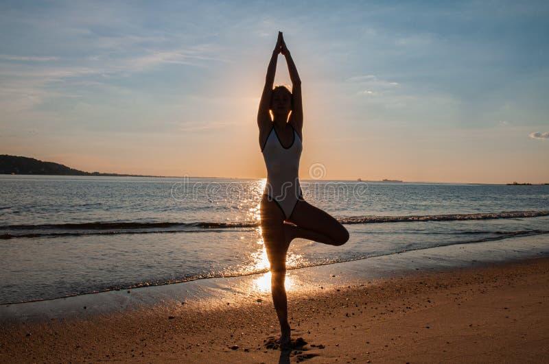 De yoga van de silhouetvrouw op het strand bij zonsondergang De vrouw oefent yoga bij zonsondergang op overzeese kust uit stock afbeelding