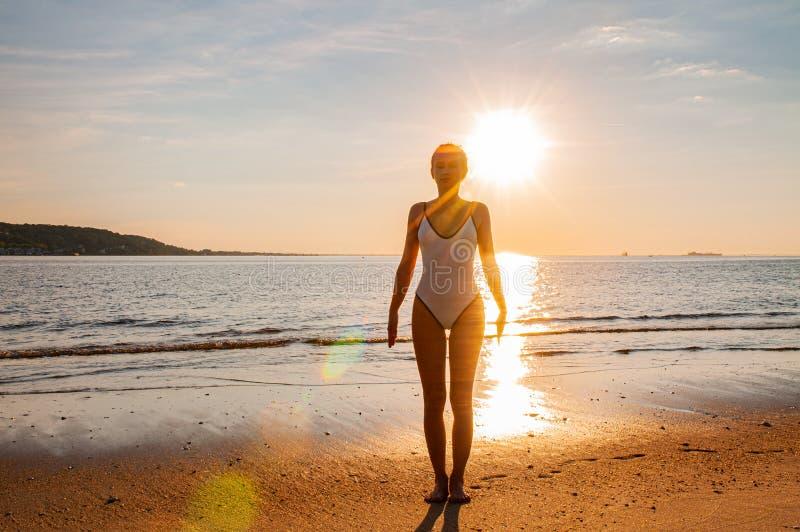 De yoga van de silhouetvrouw op het strand bij zonsopgang De vrouw oefent yoga bij zonsondergang op overzeese kust uit stock fotografie