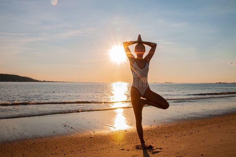 De yoga van de silhouetvrouw op het strand bij zonsopgang De vrouw oefent yoga bij zonsondergang op overzeese kust uit stock foto's