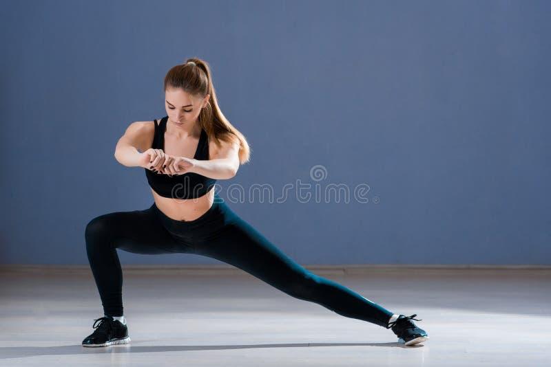 De yoga van vrouwenpraktijken in een opleidingszaal stock fotografie
