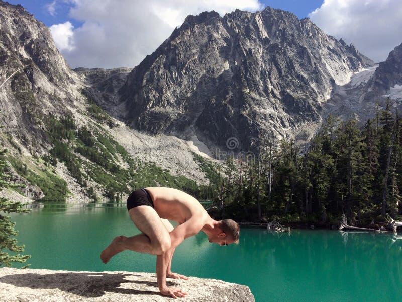 De yogakraai stelt door smaragdgroen meer royalty-vrije stock fotografie