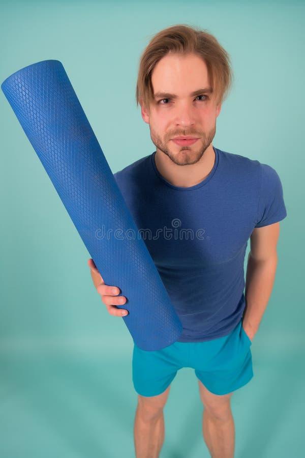 De yogamat van de mensengreep Manieratleet in blauwe t-shirt en borrels Sportman met modieus varkenshaar en haar Gymnastiekmateri stock foto's