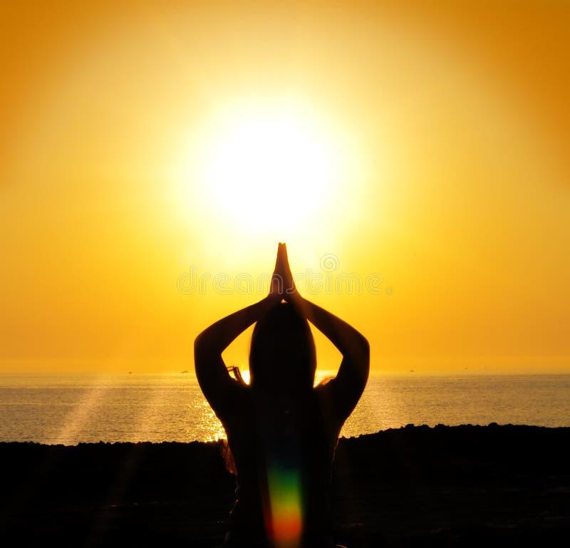 De yogasilhouet van de vrouw in de zon stock afbeeldingen