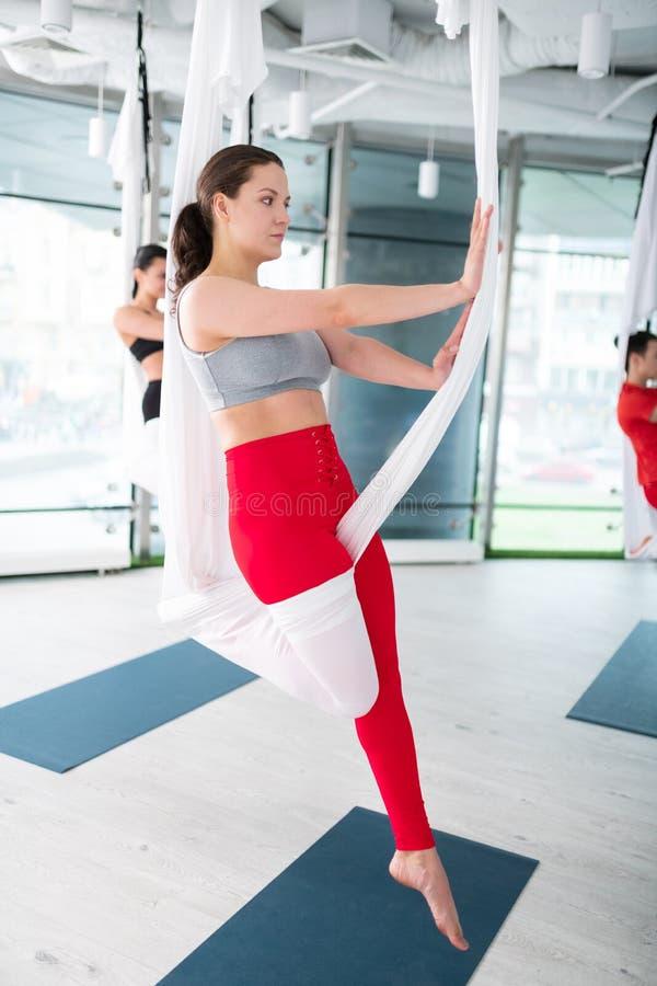 De yogatrainer die het hoogste tonen dragen stelt voor antigravity yoga stock afbeelding