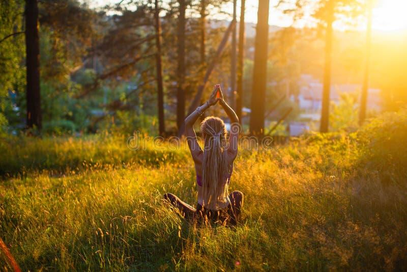 De yogavrouw mediteert in een opheldering in het hout ontspan stock fotografie