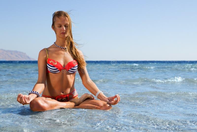 De yogavrouw van de blonde het mediteren door het overzees stock afbeeldingen
