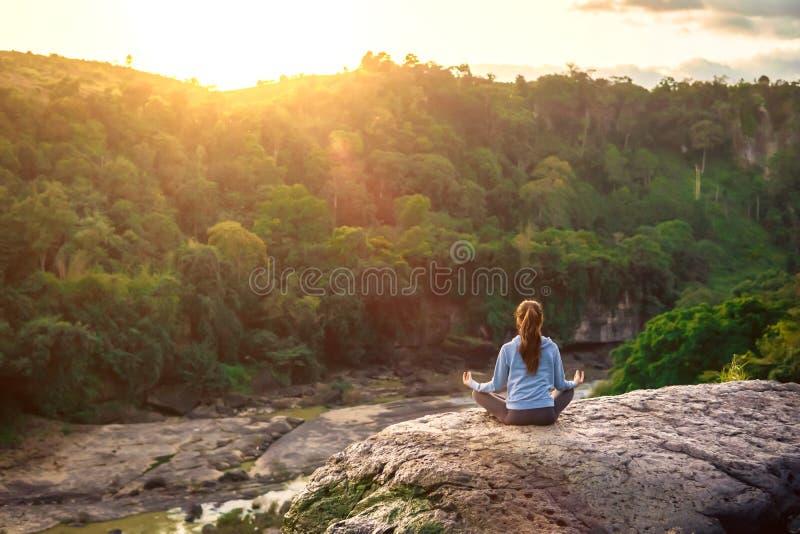 De yogavrouw zit in lotusbloem stelt op berg piekrots bij zonsopgang royalty-vrije stock foto's