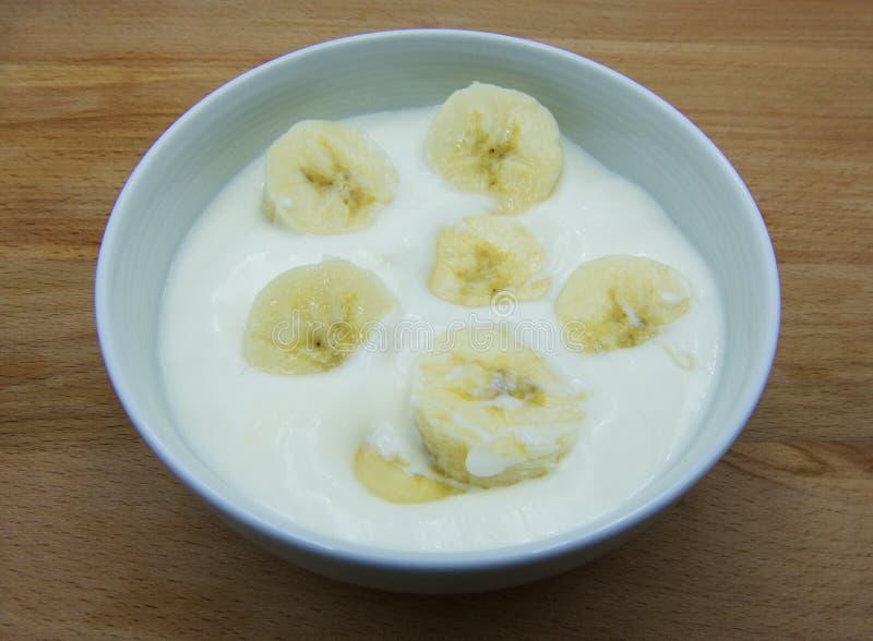 De yoghurt van de huisbanaan in een witte ceramische kruik, houten achtergrond stock foto