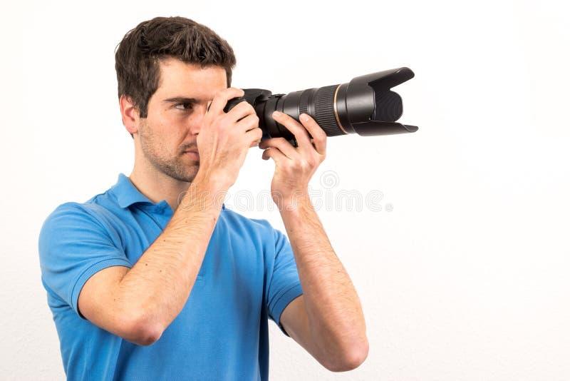 De Younffotograaf kijkt zijdelings door zijn camera royalty-vrije stock afbeeldingen