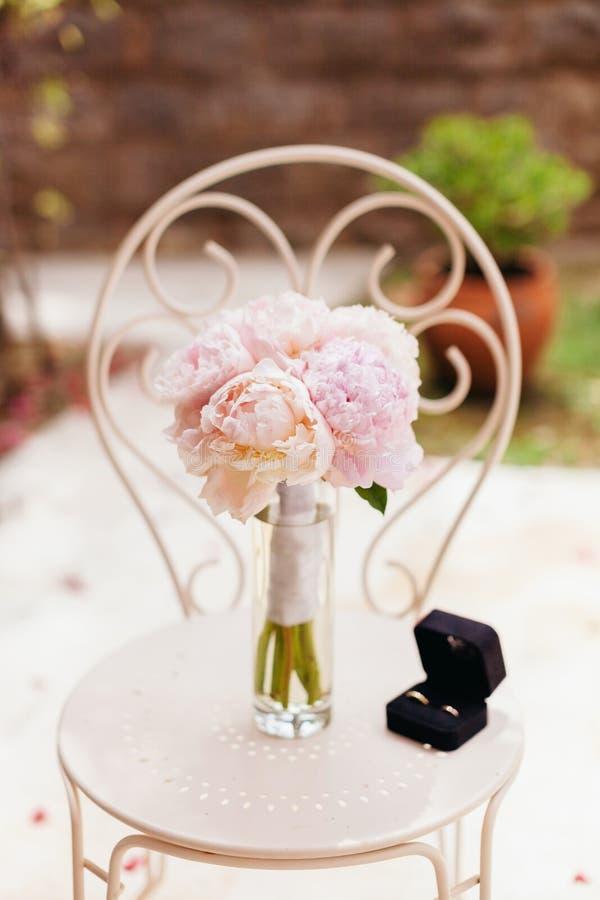 De zachte pioenen van het huwelijksboeket met ringen stock afbeeldingen