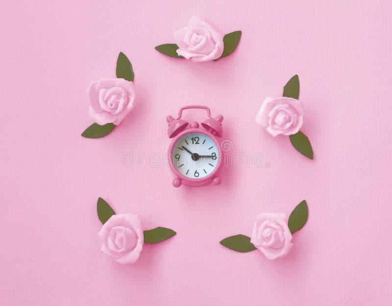 De zachte roze document textuurachtergrond met wekker, nam toe royalty-vrije stock foto's