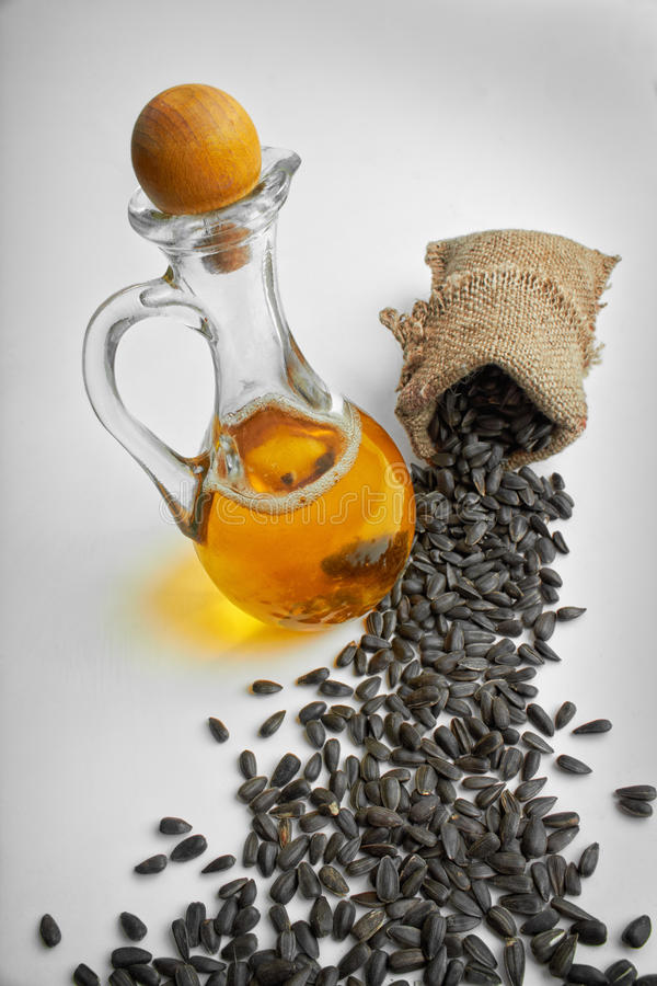 De zaden van de zonnebloem en plantaardige olie in een fles stock afbeelding